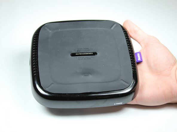 Place the Roku 4 face-down on a table. The rubber sticker should be facing you.