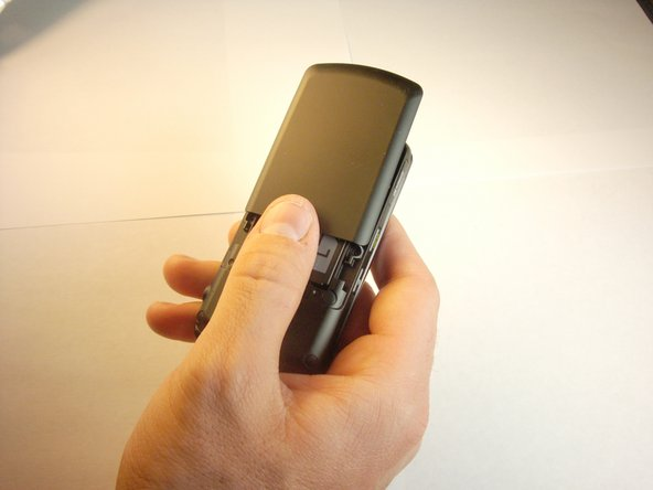 Push from indentation and slide battery cover away from phone to remove battery cover.