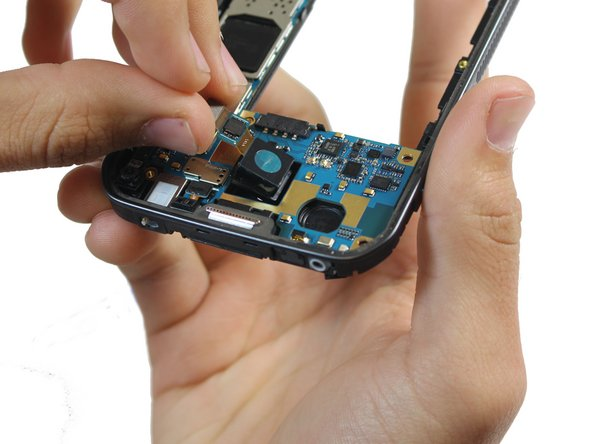 Use your hands to gently remove the rear-facing camera from the motherboard.