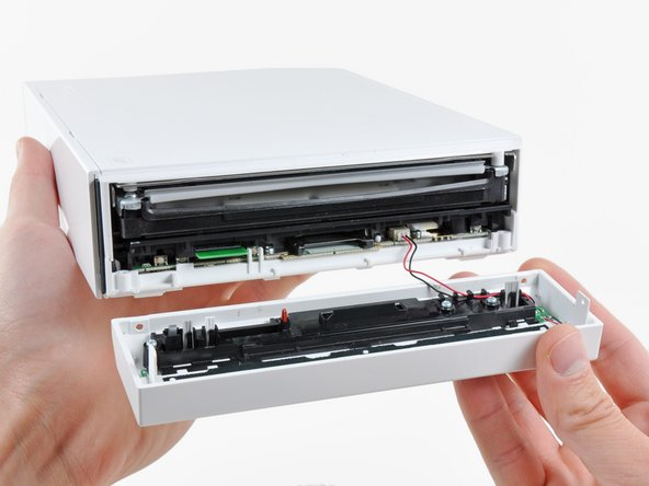 Carefully pull the faceplate away from the front of the Wii.
