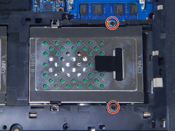 Locate the metal hard drive bay in the bottom left corner of the laptop.