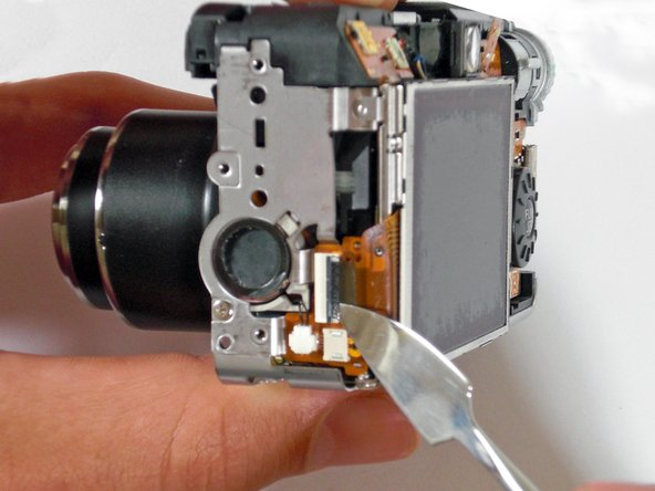 With the spudger, gently lift the black flap that is holding the wide ribbon cable wire in place.
