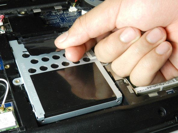 To remove the hard drive from the computer, grab the black tab attached to the hard drive and pull the tab downwards toward the bottom of the laptop.