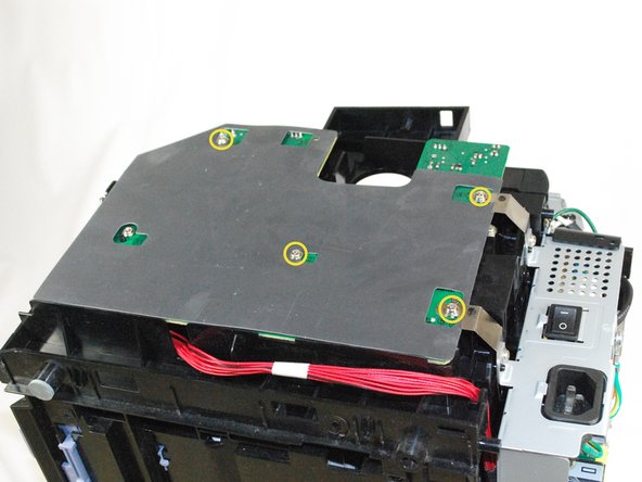 "Using a Phillips #2 screwdriver, remove the four 1"" screws attaching the gray plate to the printer."