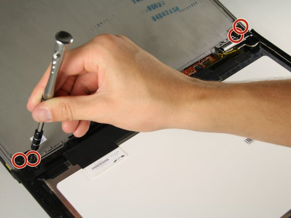 """Remove the four 1/8"""" screws using a Phillips #00 screwdriver from the hinge on either side of the laptop."""