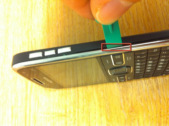 I used the opening device to un clip the silver front of the phone by inserting it at the point shown in the image and then running it down the side of the phone downwards (towards the bottom).