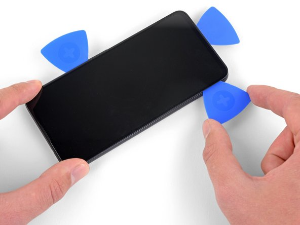 Insert another opening pick into the bottom edge of the phone at an angle where a gap has already formed to prevent damage to the OLED panel.