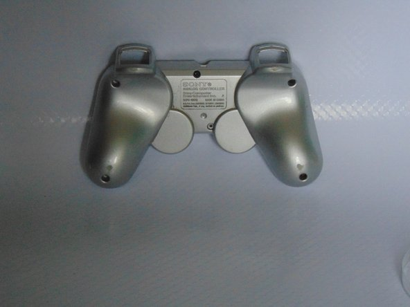 Using a pry tool separate the two controller pieces
