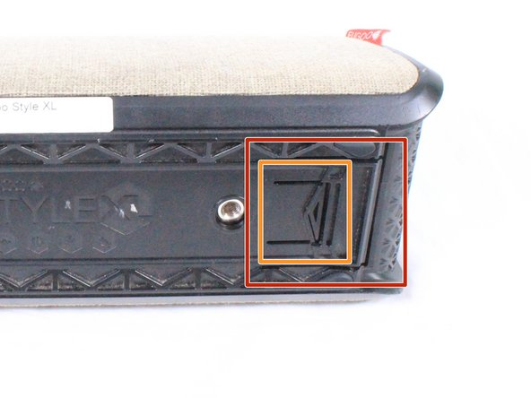 Using your hand, gently lift the large plastic tab secured to the rubber holding. The holding is shown in the  orange box of the first image. After lifting the tab, slide the speaker out of its case.