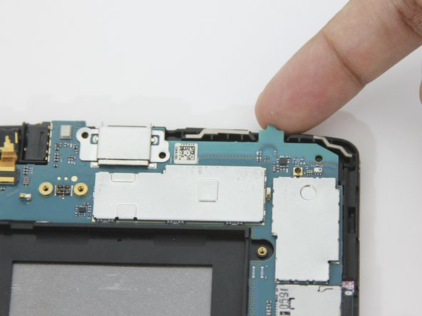 With your fingers, lift up the motherboard from the upper right corner.