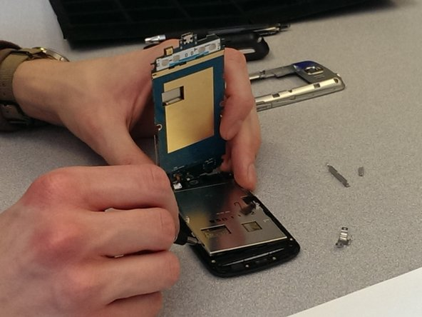 Loosen the screen from the frame at one of four corners using a flat head screwdriver.