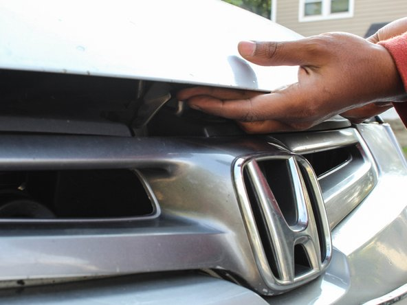 Identify the release latch beneath the hood. For the 2003 model this is located directly above the Honda logo that is on the grill.