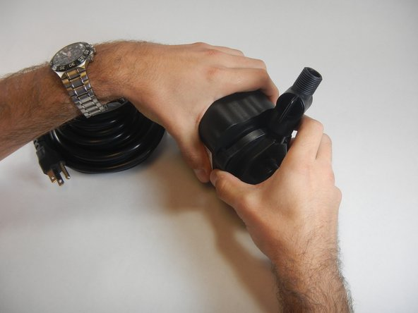 Firmly hold the pump block with one hand and the impeller housing with the other hand. Rotate impeller housing counterclockwise until it is released.