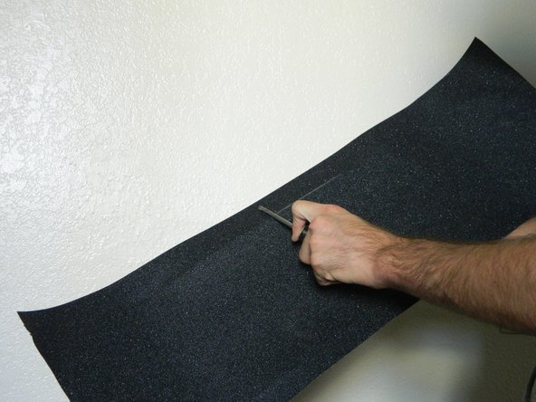 Use a screwdriver to scrape along the edges of the skateboard.  This will remove some of the grip around the edges making the trimming process easier on you and your equipment.