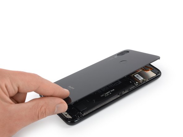 Carefully fold the rear glass to the left side of the phone assembly like you'd open the front cover of a book.
