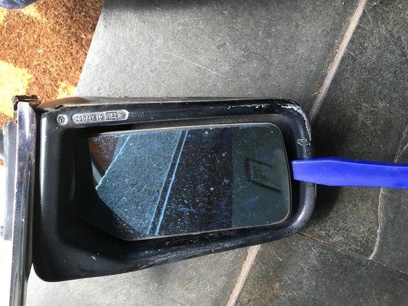 Con la regulación del cristal  a tope hacia la derecha, introducir una herramienta plastica, o destornillador encintado,  y hacer palanca suavemente. El espejo tiene un soquete donde encastra un pin circular que lo sostiene en su lugar