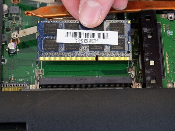 Slide the RAM out of the slot carefully.