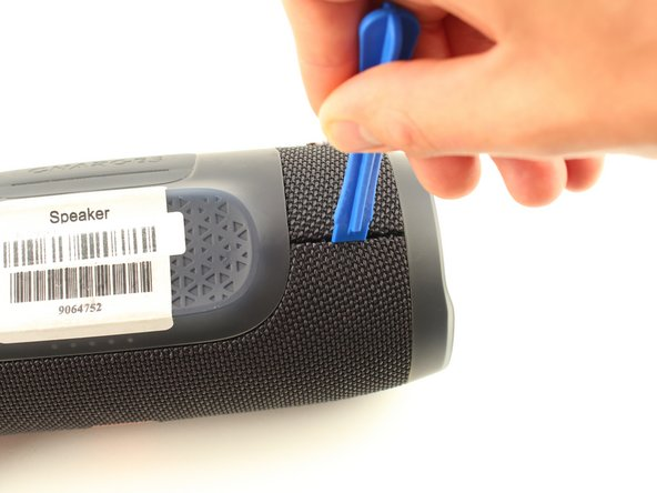 Turn your speaker upside down and insert the plastic opening tool vertically into the slit in the front cover.