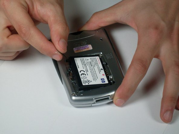 Pull on the black tab to lift the battery out of the battery compartment.