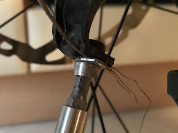 Im zweiten Schritt, lösen wir die Schraube, welche den Schaltzug im Schaltwerk klemmt. Nun sollte der Schaltzug locker und ohne Spannung sein.