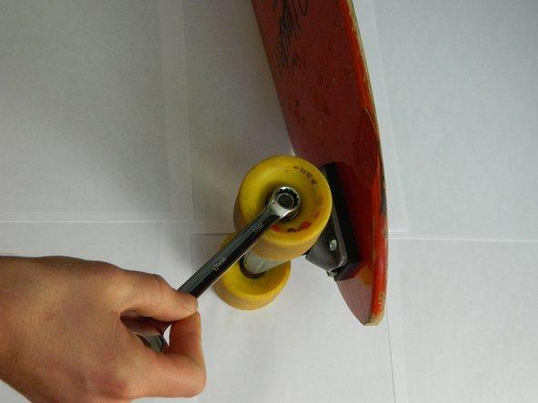 Drehe die Achsmutter mit einem 13 mm Schlüssel heraus.