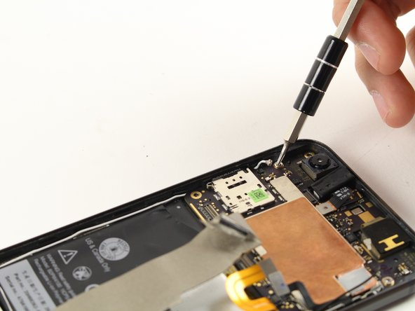 Remove the two silver 2.5 mm T5 screws holding the motherboard in place.