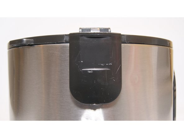 Locate the piece on the black plastic trim that is opposite from where the hinges were. Carefully, pry this piece from the bottom to get the tab from behind the stainless steel to in front of the steel as shown.