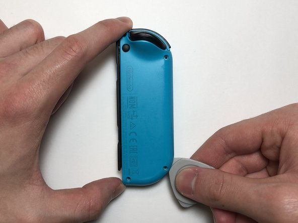 Insert the opening pick into the bottom of the Joy-Con, then move it towards the L and ZL buttons.