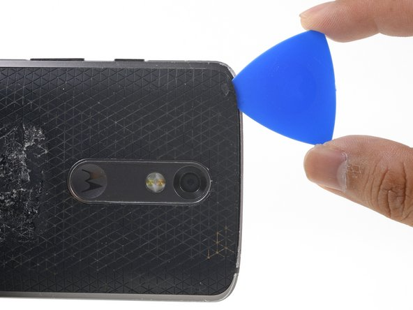 Slide the opening pick along the top edge of the phone to break up the adhesive.