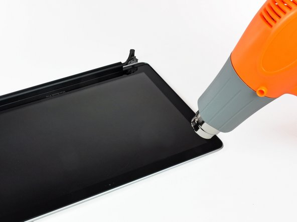 Use a heat gun to soften the adhesive under the black strip near the upper left corner of the glass display panel.