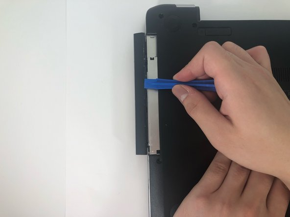 Use the iFixit opening tool to slide the optical drive away from the laptop housing.