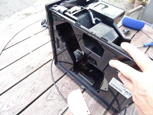 Setze ein Kunstoffwerkzeug in den Spalt zwischen Vorderseite und rechtem Seitenteil ein und vergrößere ihn. Schiebe dann das Seitenteil nach hinten. Das Seitenteil klemmt oft sehr stark und du musst viel Kraft aufwenden.