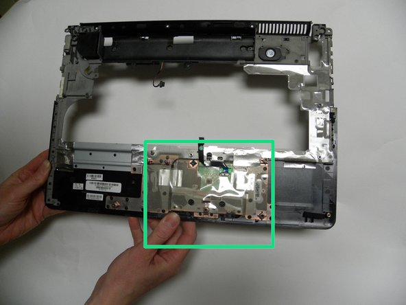 Now that the top cover is removed, check for debris or food particles that may have become trapped underneath the top cover's TrackPad button area.