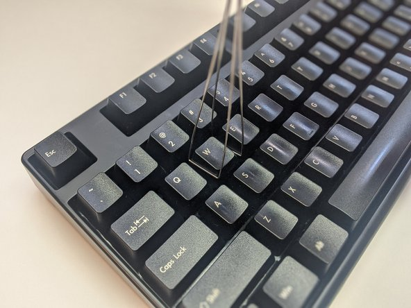 Insert the key cap puller into the cracks around the keycap.
