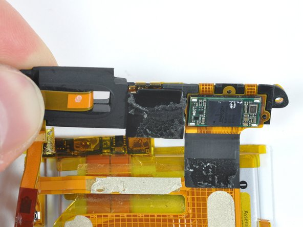 It appears that Apple left in room for a camera in the top of the device. There is a 6mm × 6mm × 3mm space between the Broadcom chip and the wireless antenna. There isn't enough depth for an iPhone-style autofocus still camera, but just enough room for the camera that Apple used in the 5th generation iPod nano.