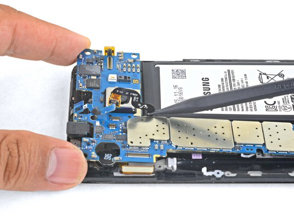 Holding the motherboard by the top corners, hinge it upwards while clearing flex cables out of its path.