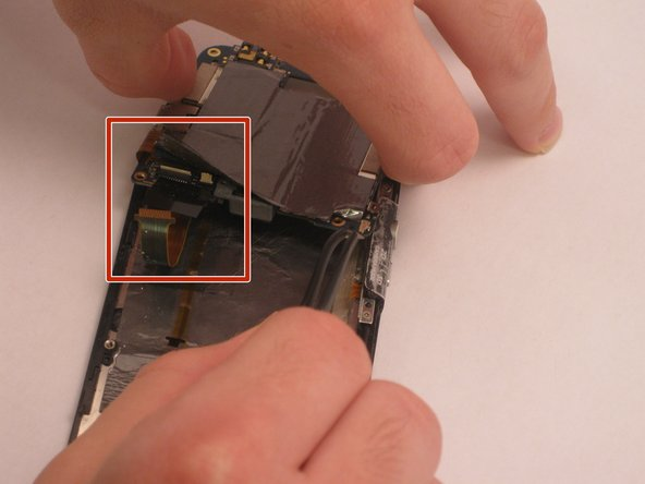 Disconnect the two ribbons on the backside of the mother board using precision tweezers.