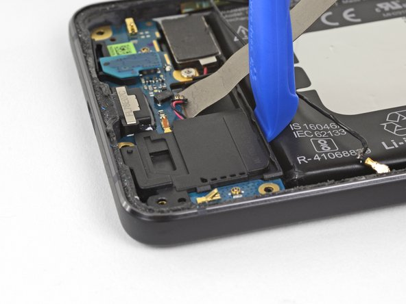 Use an opening tool to pry the loudspeaker assembly up slightly from its recess in the phone.