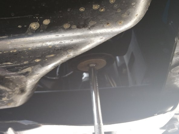 Using the 3/8 inch socket wrench with extension, loosen the oil filter by putting the extension in the square hole in the filter and turning counterclockwise.