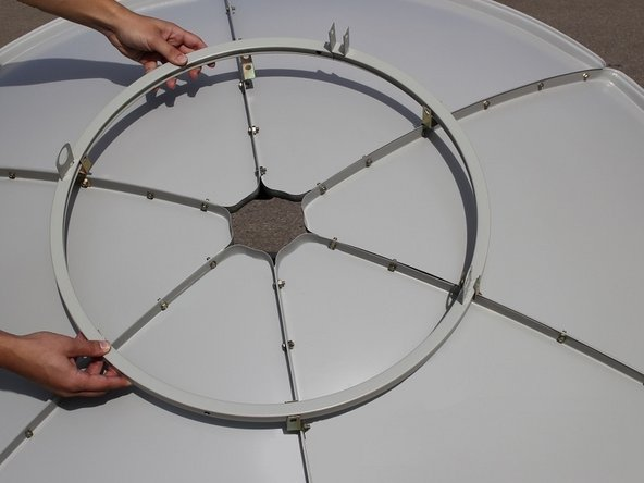 Place the assembled solar panel dish face down with the metal brackets on the top and facing up.