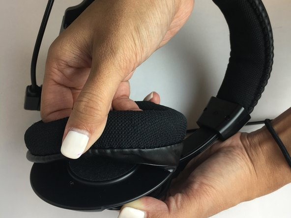 Grip ear cushion and carefully pull up and separate from the plastic headphone.