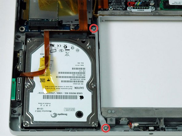 Remove the two T6 Torx screws securing the hard drive retaining bracket to the lower case.