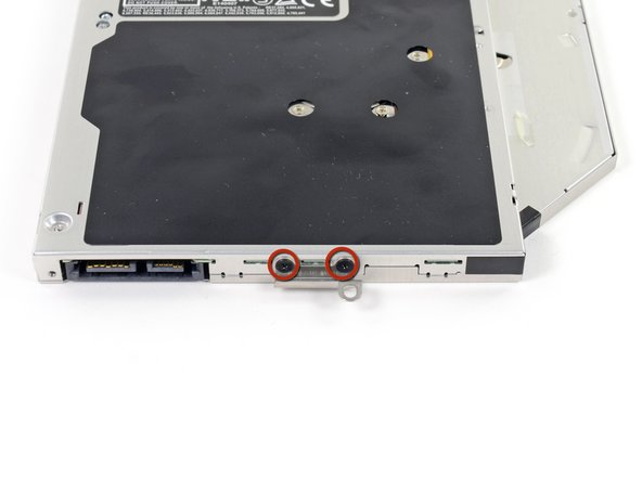 Remove the two black Phillips #0 screws securing the small metal mounting bracket. Transfer this bracket to your new optical drive or hard drive enclosure.