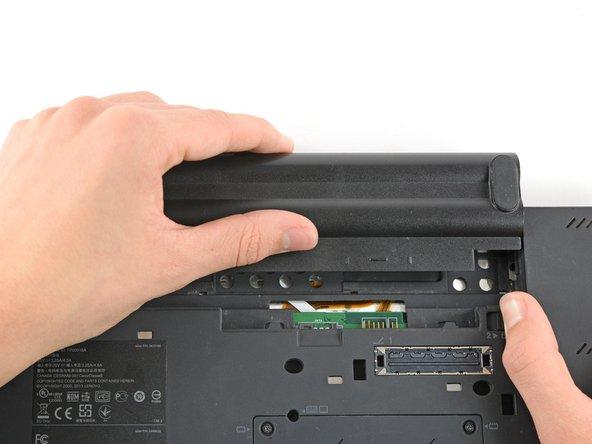 现在按住右侧的开关向右拨,并使用另一只手轻轻地将电池向上滑出笔记本电脑。