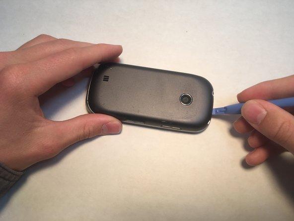 Avant de terminer cette étape, assurez-vous que votre appareil est éteint. Une fois qu'il est éteint, retirez délicatement le couvercle arrière du téléphone en faisant levier sous le clip près de l'appareil photo.