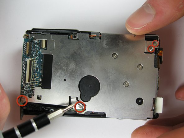 Remove the two 3x2 screws and two 3.5x2.5 screws attaching the rear panel to the motherboard.