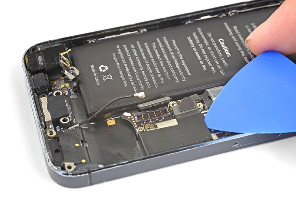 Slide an opening pick underneath the Lightning connector flex cable to loosen it from the logic board and the rear case.