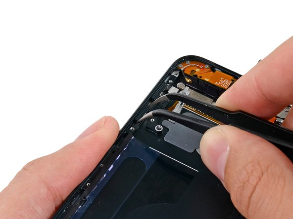 Use tweezers to remove the volume-down button from the iPod.