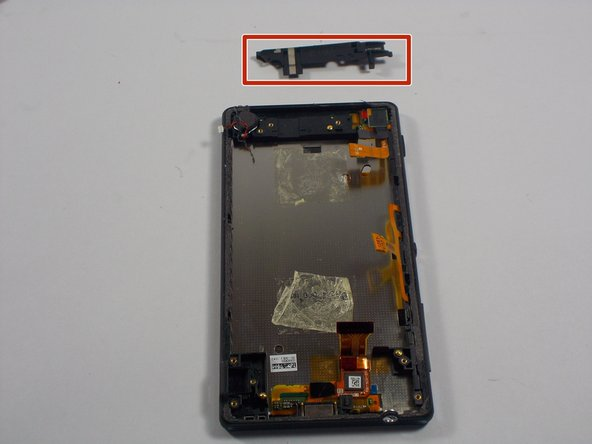 With the battery out. You will want to pry out the plastic covering on the top side of the phone.
