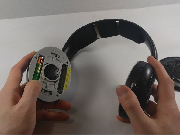 Twist the left ear pad counterclockwise to reveal the battery compartment within the headphone.